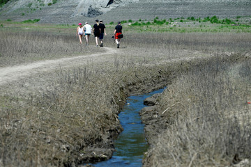 People walk across the dried out lakebed of the Edersee reservoir near Asel