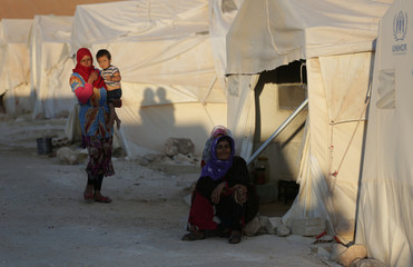 Internally displaced woman sits outside a tent in Idlib province