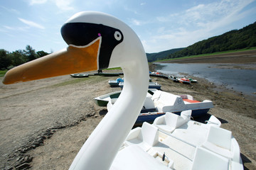 Paddle boats lie on the banks of the dried up lakebed of the Edersee reservoir near Asel