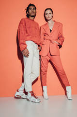 Casual couple in red leaning against a red wall