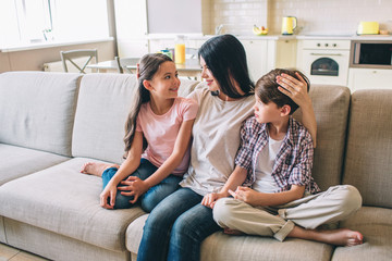 Mother is sitting on sofa with her kids. She is hugging them. Woman looks at daughter. She holds hand on boy's head. Happy kids are looking at mom.