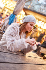 Portrait of a smiling beautiful young woman while sitting in a christmas market.