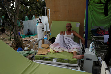 A man sits on a bed at Tanjung hospital after earthquake hit on Sunday in North Lombok