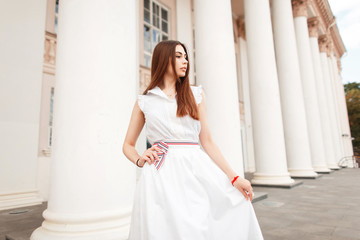 Pretty young woman in white fashionable dress posing near column