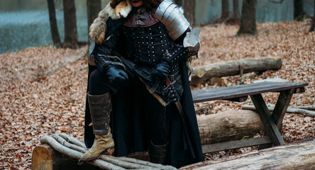Medieval knight with sword in armor as style Game of Thrones in the forest.holds the sword