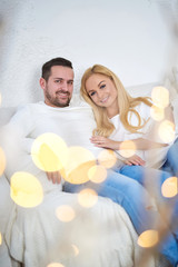 A beautiful happy young couple sitting on the sofa in the living room with christmas lights.