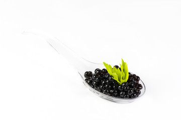 Plastic spoons with fish caviar on a white background.