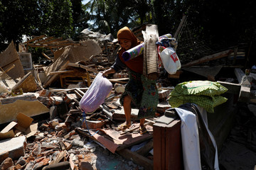 A woman carries valuable goods from the ruins of her house at Kayangan district after earthquake hit on Sunday in North Lombok