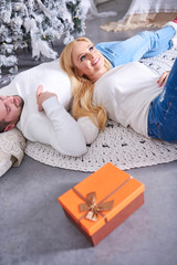 A beautiful happy young couple laying on the ground with the christmas tree and the presents.