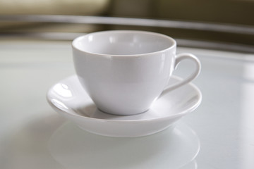 An empty white cup and a saucer stand on a coffee table.