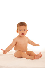 Hapy baby boy in playing on bed isolated over white