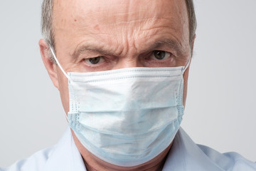 Close up portrait of serious man in special medic mask. He is looking serious. Mature experienced doctor.