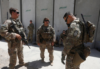 U.S. troops wait at their base to fly to a training and advisory mission at an Afghan National Army (ANA) Base in Logar province