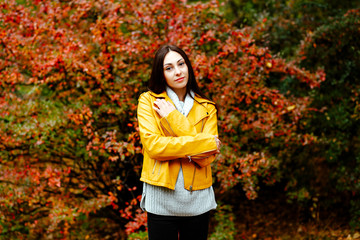 Autumn portrait of a girl in the Park. Young brunette woman walking in the autumn Park, cluttering in a yellow jacket.