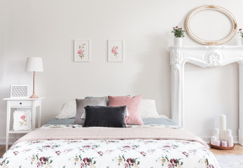 Real photo of bright feminine English style bedroom interior with double bed, simple roses posters, mockup frame and faux fireplace with candles