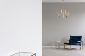 Gold chandelier above blue armchair in elegant living room interior in blurred background. Real photo with focus on an empty place on the wall for your product