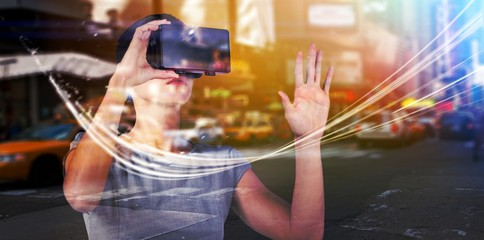 Composite image of young woman wearing virtual video glasses