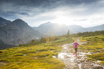 Woman trail running in the Indian Peaks wilderness on Arapahoe pass trail in Colorado.