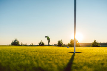 Full length view of the silhouette of a male player, hitting a long shot on the putting green of a professional golf course of a modern country club