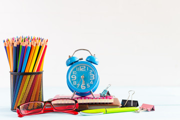 Education or back to school Concept. school office supplies. alarm clock, colorful pencils in yellow mug on white wooden background.