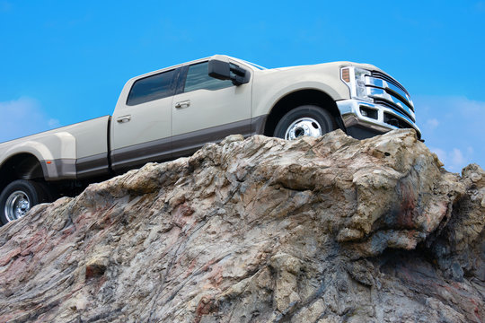 Big rugged pickup truck driving on the edge of a rocky cliff ledge with a bright blue sky in the background.