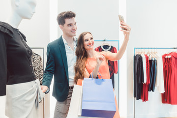 Couple doing selfie phone photo with their catch in fashion store