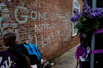 A boy passes tributes written at the site where Heather Heyer was killed during the 2017 white-nationalist rally in Charlottesville
