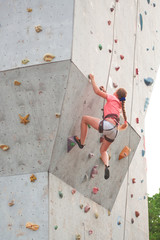 girl climbing up a high wall for rock climbing
