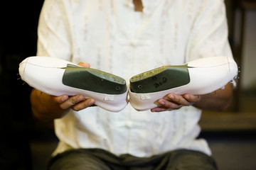 Cobbler Cai Wenke inspects a pair of 'thousand-layer' cloth shoes at the demonstration workshop of the Neiliansheng shoemaker in Beijing
