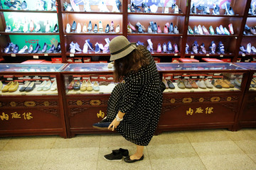 A customer tries on a handmade 'thousand-layer' cloth shoe at the showroom of the Neiliansheng shoemaker in Beijing