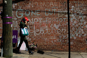 A woman walks past tributes written at the site where Heather Heyer was killed during the 2017 white-nationalist rally in Charlottesville