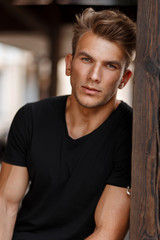 Handsome young male model with a hairstyle in a black stylish T-shirt near a wooden pillar outdoors
