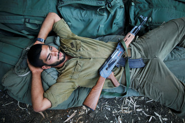 An Israeli soldier lays down during an army drill after the visit of Israeli Defence Minister Avigdor Lieberman in the Israeli-occupied Golan Heights