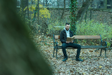 A retro style photo of a young hipster man sitting on a bench and reading a book in the park.