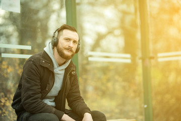 A retro style photo of a young hipster man waiting at the bus stop while listening to music on his headphones.