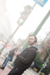 A handsome young hipster man checking his smartphone while waiting at a crosswalk.