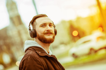 A retro style portait of a smiling young hipster man in an urban environment.