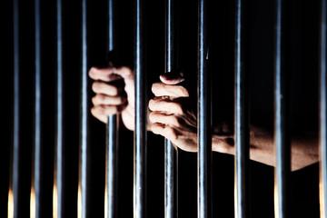 close up of prisoner hands in jail.