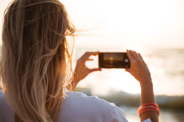 Back view of a woman taking a picture of a sunset