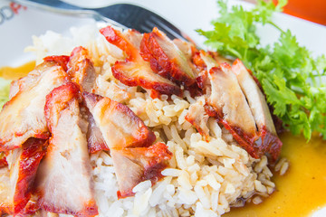 Barbecued red pork in sweet sauce with rice and cucumber on table