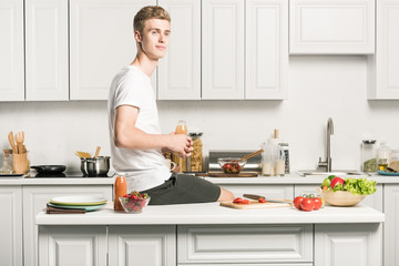 handsome young man sitting on kitchen counter and holding healthy juice in bottle