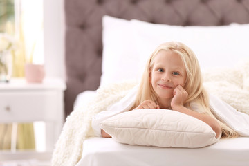 Cute little girl with pillow lying in bed at home