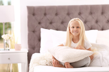 Cute little girl with pillow sitting on bed at home