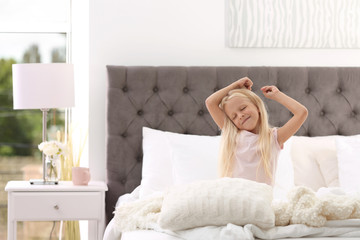Cute little girl stretching in bed with pillows at home
