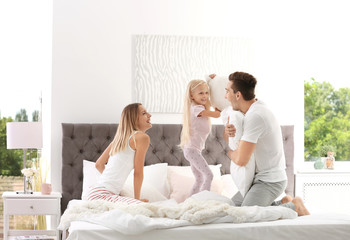 Happy family having pillow fight on bed at home