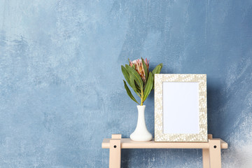 Blank frame and vase with flower on table near color wall. Mock up for design
