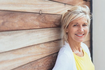Smiling blond woman leaning on a wooden wall