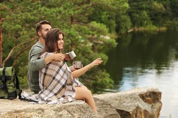 Cute couple with mugs and plaid near lake. Camping season
