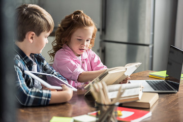 little brother and sister with devices reading book together