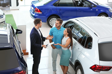 Salesman consulting young couple in car salon